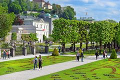 Mirabell Palace and Gardens in Salzburg, Austria. Salzburg, Austria - May 23, 2018 : people walk among flower beds in the Mirabell park in Salzburg royalty free stock photo