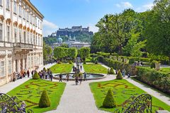 Mirabell Palace and Gardens in Salzburg, Austria. Salzburg, Austria - May 23, 2018 : people walk among flower beds in the Mirabell park in Salzburg, old historic stock photo