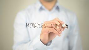 Miracels geschehen, bemannen Schreiben auf transparentem Schirm stockfoto