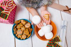 Miracle for child. Christmas festive food. Favorite time of year, unrecognizable kid with tasty sweets on wooden background. Yummy presents top view, joyful Royalty Free Stock Photography