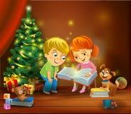 Miracle de Noël - enfants lisant le livre près d'un arbre de Noël Photo stock