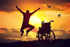 A miracle happened. Disabled handicapped man is healthy again. He is happy and jumping at sunset.  stock photos