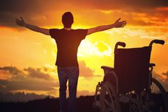 A miracle happened. Disabled handicapped man is healthy again. He is happy and standing at sunset Royalty Free Stock Image