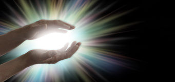 Miracle maker. Pair of parallel female healer's hands with a bright white and rainbow colored light energy formation between, on a wide black background with Stock Photos