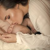 Miracle of motherhood. Woman sleep with infant child boy. Mother hug baby son asleep on blanket. Mothers day concept. Family, love, protection, trust. Dream royalty free stock photo