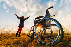 Miracle recovery II: young girl gets up from wheelchair and raises hands up Royalty Free Stock Images