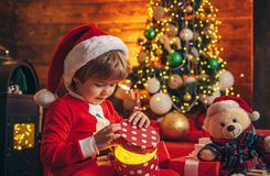 It is miracle. Santa boy little child celebrate christmas at home. Lovely baby enjoy christmas. Family holiday. Boy cute. Child cheerful mood play near stock image