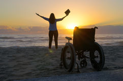 Miracle spiritual healing crippled woman walking at beach at sun. Miracle spiritual healing crippled woman praying with bible stands up out of wheelchair and Royalty Free Stock Image