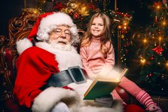 Miracle time at christmas. A happy young girl is sitting with Santa Claus at home. Merry Christmas and Happy New Year. Miracle time stock photos