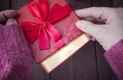 A woman opens a red gift and there is a bright light. A miracle. a woman opens a red gift, and there is a bright light Stock Image