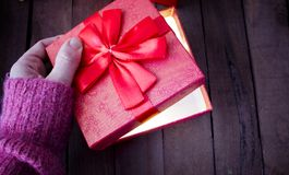 A woman opens a red gift and there is a bright light. A miracle. a woman opens a red gift, and there is a bright light Royalty Free Stock Photos