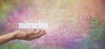 Miracles Happen. Female hand outstretched palm up with the word 'Miracles' above surrounded by a word cloud of relevant words on a pastel colored stone effect