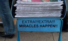 Miracles happen. Newspaper stack - take one of these newspaper in the subway entrance- miracles happen royalty free stock images