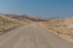 Mirada abajo del camino de tierra a las colinas pintadas Fotografía de archivo
