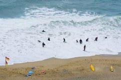 Mirada abajo en el grupo de personas que practica surf en wetsuits en la playa Foto de archivo