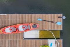 Mirada abajo en un muelle en el agua con un kayack y paletas y chalecos de vida al lado de una plataforma lanching del kayac foto de archivo libre de regalías