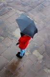 Mirada abajo en una mujer que usa un paraguas en un día mojado Fotos de archivo