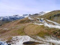 Mirada abajo a la trayectoria con el cerco de las montañas coronadas de nieve Foto de archivo