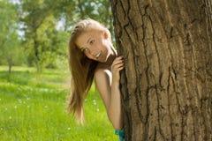 Mirada adolescente de la muchacha hacia fuera del árbol en parque Imagen de archivo