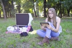 Mirada adolescente de la mujer joven a una foto cerca de la maleta con ropa Fotos de archivo libres de regalías