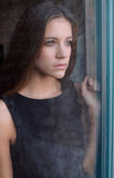 Mirada adolescente hermosa a través de ventana Fotografía de archivo libre de regalías