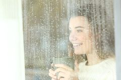Mirada adolescente sonriente a través de una ventana en un día lluvioso Fotos de archivo