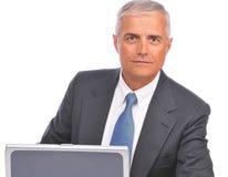 Mirada asentada hombre de negocios sobre la tapa de la computadora portátil Foto de archivo