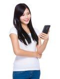 Mirada asiática de la mujer en el teléfono móvil fotografía de archivo