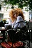 Mirada atractiva de una mujer joven en un café del estilo de París Fotos de archivo