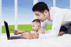 Mirada curiosa del bebé en la pantalla del ordenador portátil Imagen de archivo