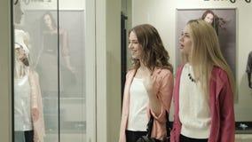 Mirada de dos muchachas en una demostración-ventana de la tienda almacen de metraje de vídeo