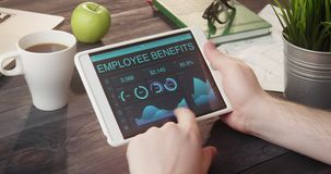 Mirada de expedientes de las ventajas de empleado usando la tableta digital en el escritorio almacen de metraje de vídeo