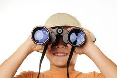 Mirada de exploración del muchacho a través de los prismáticos Fotografía de archivo libre de regalías