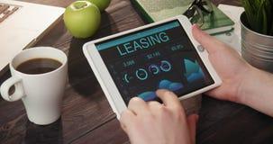 Mirada de gráficos y de cartas del alquiler con opción a compra usando la tableta digital almacen de video