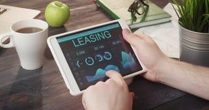 Mirada de gráficos y de cartas del alquiler con opción a compra usando la tableta digital en el escritorio almacen de metraje de vídeo