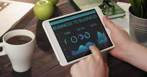 Mirada de gráficos y de cartas interempresariales usando la tableta digital almacen de metraje de vídeo