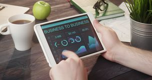 Mirada de gráficos y de cartas interempresariales usando la tableta digital en el escritorio almacen de video