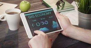 Mirada de la información de la economía del carruaje usando la tableta en el escritorio