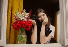 Mirada de la muchacha del adolescente fuera de la ventana en la mañana Imagenes de archivo