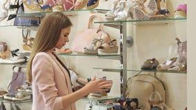 Mirada de la muchacha en el precio de los zapatos en la tienda almacen de metraje de vídeo