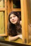 Mirada de la muchacha fuera de la ventana de madera Fotografía de archivo