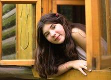 Mirada de la muchacha fuera de la ventana de madera Fotografía de archivo libre de regalías