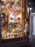 Mirada de la muchacha a través de la ventana de la tienda de souvenirs en el bazar del este en Egipto imágenes de archivo libres de regalías