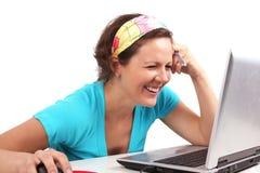 Mirada de la mujer de Smilling en la computadora portátil Imagen de archivo libre de regalías