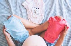 Mirada de la mujer embarazada de la ropa del bebé Foto de archivo