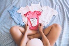 Mirada de la mujer embarazada de la ropa del bebé Imagen de archivo