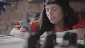 Mirada de la mujer joven en el teléfono móvil en la fabricación y alguien de los muebles darle un tiro del compresor en la cara almacen de video