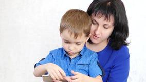 Mirada de la mujer y del niño en la pantalla del smartphone y de la risa La mamá juega con su hijo en un juego que se convierte V almacen de video