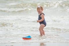 Mirada de la parte posterior de un bebé en la playa con un juguete del barco Imagen de archivo libre de regalías