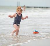 Mirada de la parte posterior de un bebé en la playa con un juguete del barco Fotos de archivo